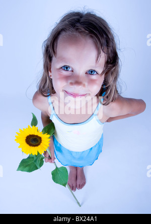 A little girl holding in her hand a beautiful flower - Stock Photo