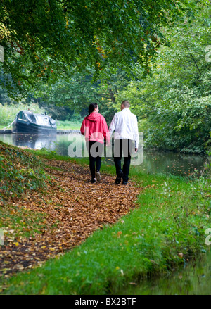Couple walking hand in hand along canal towpath away from camera with canal and narrowboat or barge moored up ahead - Stock Photo
