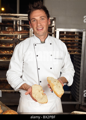 Smiling baker showing a nice porous structure a freshly baked bread sliced in halves - Stock Photo