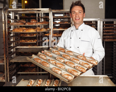 Portrait of a baker holding a tray with freshly baked buns in a bakery - Stock Photo