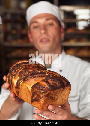 Baker looking at a freshly baked loaf of sweet bread in his hands. Focus is on the bread. - Stock Photo