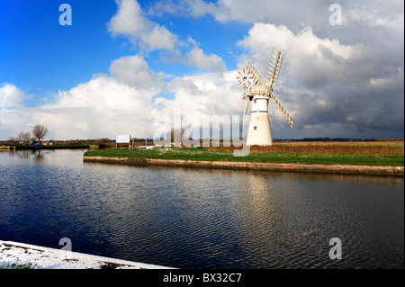 Thurne Mill and reflection on the Norfolk Broads in winter set against a threatening sky. - Stock Photo