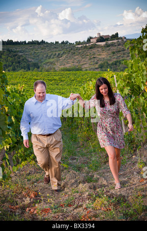 Couple walking hand in hand in a vineyard Tuscany Italy - Stock Photo