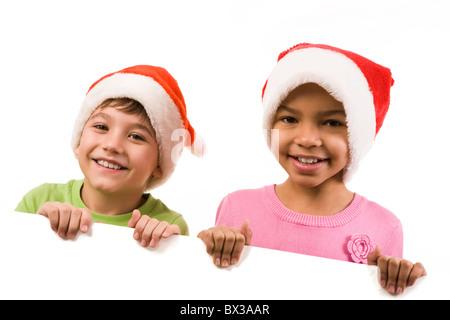 Photo of happy friends in Santa caps smiling at camera - Stock Photo