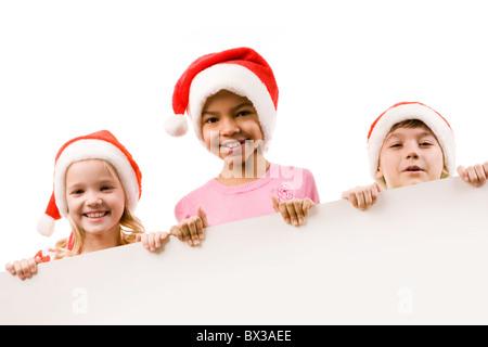 Photo of happy friends in Santa caps peeking into camera - Stock Photo