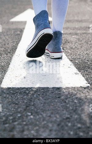 detail of young girl standing on arrow sign on road - Stock Photo
