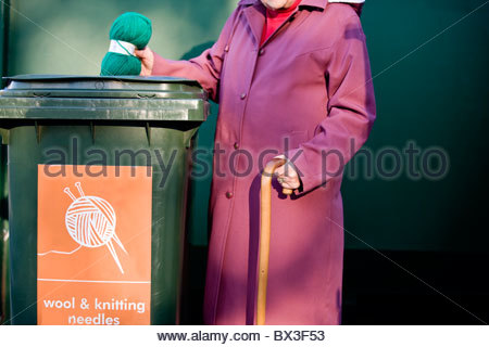 A senior woman recycling a ball of wool - Stock Photo