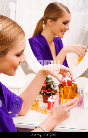 Portrait of happy girl putting small giftbox into golden package - Stock Photo