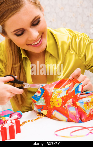 Happy woman wrapping Christmas presents before holiday - Stock Photo