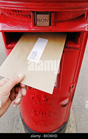 Posting a Letter Into a Post Box, UK. - Stock Photo