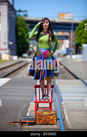 Teenage Girl Standing On A Chair Looking For The Train In Downtown: Portland, Oregon, United States Of America - Stock Photo