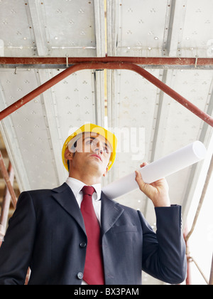 architect with scroll in construction site - Stock Photo