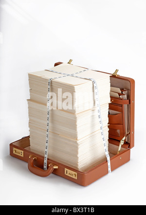 open briefcase with stacks of papers and measuring tape - Stock Photo