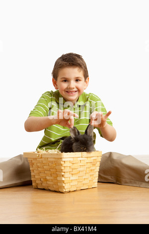 A Rabbit In A Basket And A Boy Holding It's Ears - Stock Photo