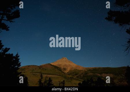 Moon Lit Mountain With Stars In The Sky; Waterton, Alberta, Canada - Stock Photo