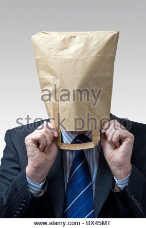 Businessman wearing a suit, shirt and tie with a brown paper bag over his head. - Stock Photo