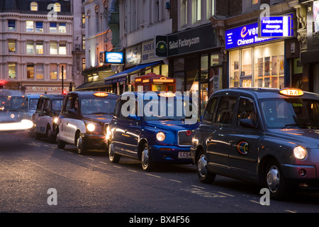 Row of black cabs taxis near Liverpoool Street Station, London, UK - Stock Photo
