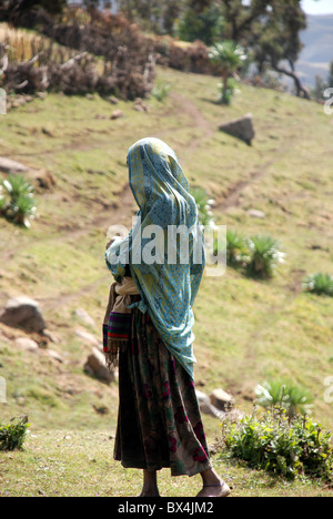 a young woman with her head covered by a blanket in the Simien mountains of Ethiopia - Stock Photo