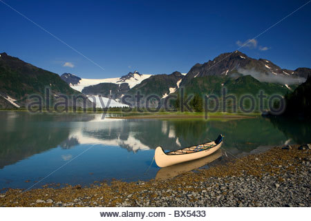 A canoe sits in waiting on a sunny day on the Lower Pedersen Lagoon, Kenai Fjords National Park. - Stock Photo