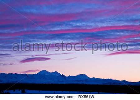 Broad Pass near Cantwell, Alaska on Parks Highway. Pink and blue sunset over snow covered mountains - Stock Photo