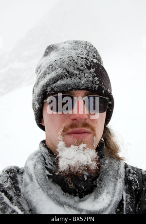 Portrait of a bearded man cover by snow in a blizzard - Stock Photo