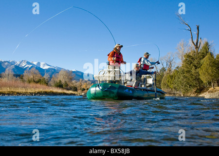 Married couple and professional guide fly fishing from a boat on the Arkansas River, near Salida, Colorado, USA - Stock Photo
