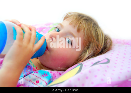 girl drinking bottle of milk laying on bed blond toddler - Stock Photo