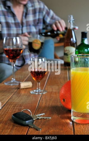 Car key, drunken man pouring beer, fruit juice and alcoholic drinks on table to illustrate responsible driving - Stock Photo
