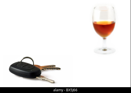 Car key and glass filled with alcohol as conceptual subjects to illustrate irresponsible driving - Stock Photo