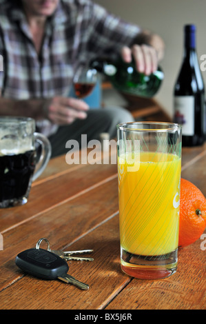 Car key, drunken man pouring wine, alcoholic drinks and soft drink on table to illustrate responsible driving - Stock Photo