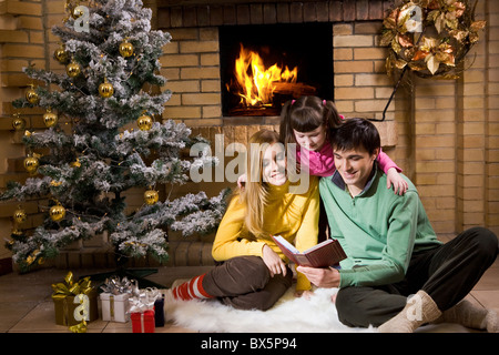 Portrait of cheerful family sitting on white fur reading old book with decorated fir tree near by - Stock Photo