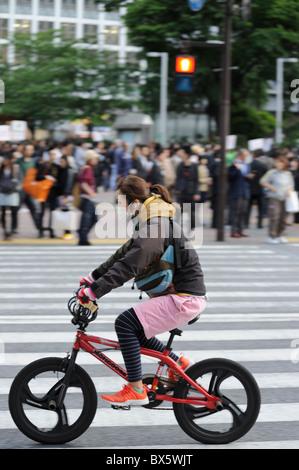 Young Japanese woman on bmx bicycle at Shibuya Crossing, Tokyo, Japan - Stock Photo