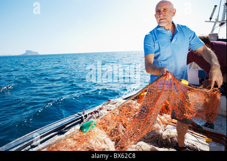 Fisherman on boat pulling in nets - Stock Photo