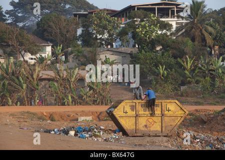 City scene along oceanfront showing children digging through trash dumpster.   Monrovia, Liberia, West Africa. - Stock Photo