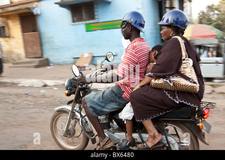 Commuters ride on the back of a motorcycl in Monrovia, Liberia, West Africa. - Stock Photo