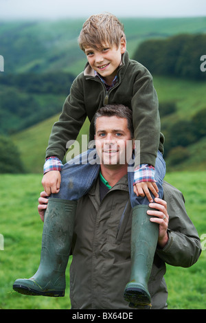 Father giving son a piggy back in field - Stock Photo