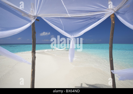 Hammock hanging in shallow clear water, The Maldives, Indian Ocean, Asia - Stock Photo