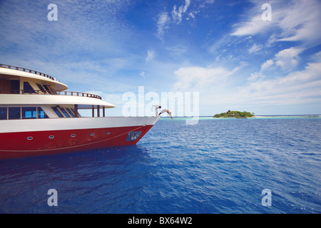 Young people jumping from boat into sea, Maldives, Indian Ocean, Asia - Stock Photo
