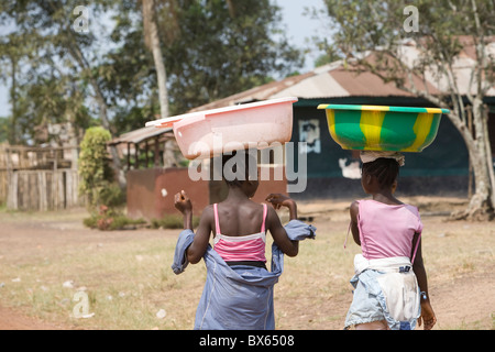 Girls with buckets balanced on their heads walk along the main street in Kakata, Liberia, West Africa. - Stock Photo