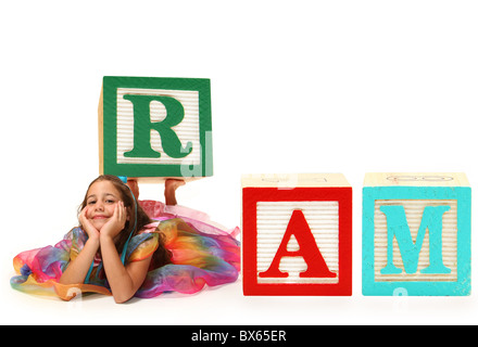Beautiful six year old girl spelling word RAM with giant alphabet blocks. - Stock Photo