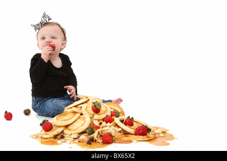 Adorable 10 month old baby girl sitting in stack of pancakes with strawberries and chocolate chips and syrup over - Stock Photo