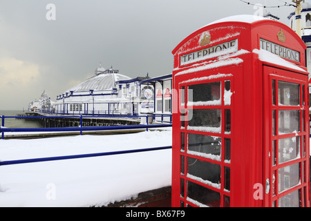 An old red telephone box  and Eastbourne Pier in the snow. - Stock Photo