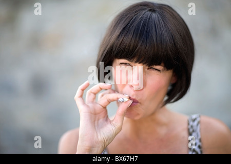 Woman smoking a cigarette - Stock Photo