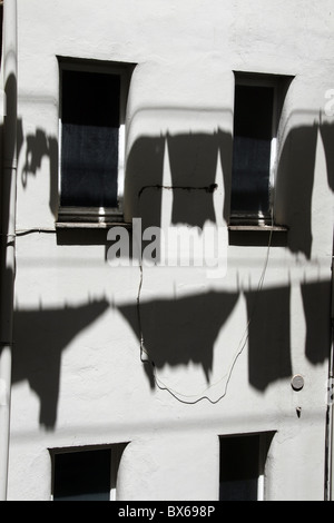shadow of clothes hanging on washing line in sun - Stock Photo