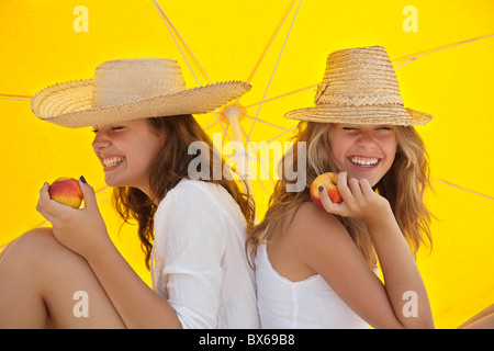 Pretty women eating fruit in the shade - Stock Photo