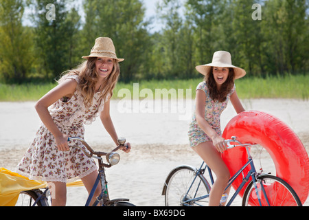 Two pretty women cycling on the beach - Stock Photo