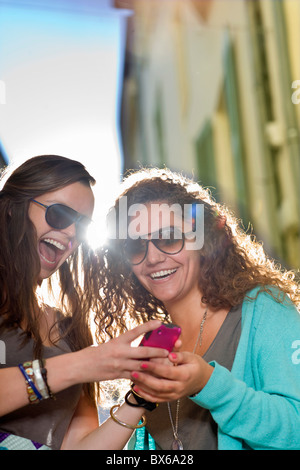 Young women share cell phone in street - Stock Photo