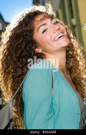 Portrait young woman laughs in street - Stock Photo