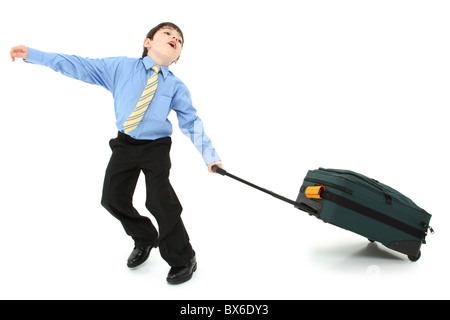 Adorable seven year old french american boy in suit struggling with large suitcase over white background. - Stock Photo