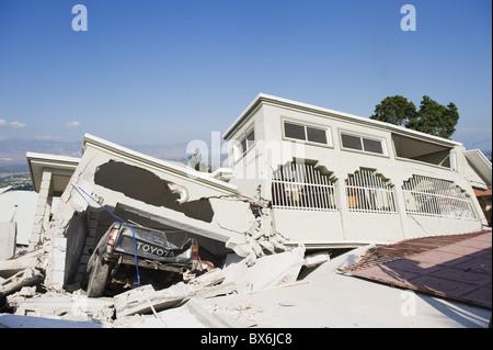 Damaged car and buildings, January 2010 earthquake, Montana Estate, Port au Prince, Haiti, West Indies - Stock Photo